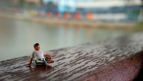 Simple, Mini figure toy old man sit at scratch wooden balcony at river side with copy or negative space for text placement area. Mini figure toy old man sit at stock images