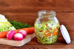 Simple mixed vegetable salad. Salad with cabbage, carrots, radish, dill and olive oil. Vegetable salad in glass jar. Vegetable salad recipe. Salad in a jar photo Stock Photo