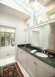 Simple modern bathroom with black granite counter. Simple modern bathroom with white tile and black granite stock images