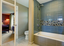 Simple yet modern bathroom interior with tile wall trim and bedroom. View Stock Images