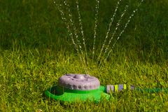 A simple and multi-functional garden sprinkler. Evening lawn irrigation. Evening lawn irrigation. A simple and multi-functional garden sprinkler royalty free stock photography