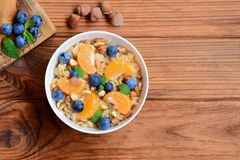 Simple Oatmeal Porridge With Fresh Mandarins, Berries, Hazelnuts And Mint In A White Bowl And On A Wooden Background Stock Photo