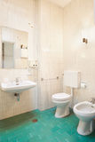 Simple, old bathroom with green tiled floor Stock Photo