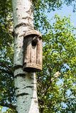 Simple old birdhouse in a rustic style. Concept of the season, guest house, own housing, natural materials. Vertical Stock Image