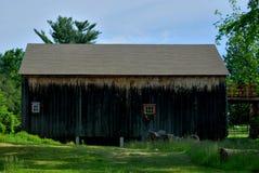 Simple old wood barn beneath deep blue sky. Dark brown red trim Stock Image