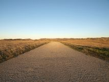 Simple Path. A simple empty gravel road through beautiful ranch grass lands Royalty Free Stock Photography