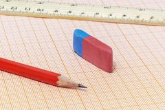A simple pencil close-up, an eraser and a ruler on a millimeter. On the millimeter paper is a simple pencil close-up with an eraser and ruler stock photo