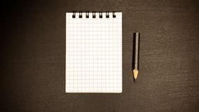 A simple pencil and a notebook on a spring on a table. A simple pencil and a blank notebook on a spring lie on the office table Royalty Free Stock Image