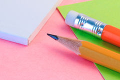 Simple pencil and paper note. Closeup pink and green paper note with wood pencil. Stock Photo