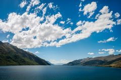 Simple Perspective background at lake Wakatipu, New Zealand. Simple Perspective background, only water, hills and puffy clouds in the sky, at Lake Wakatipu in Stock Image