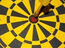 Simple pfoto image. A yellow darts board and a yellow dart in the center Stock Image