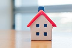 Simple plastic house model with chimney and 4 windows. On a brown wooden table Royalty Free Stock Photography