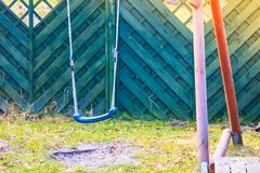 Simple, plastic swing for kids, outside shot. Playground objects and equipment concept. Simple, plastic swing for kids, outside shot Stock Photos