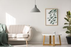 Simple poster on wall. Simple poster hanging on the wall in bright living room interior with sofa and wooden table with tea mug stock image