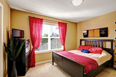 Simple yet practical bedroom design with red curtains. Simple yet practical bedroom design with dark brown bed, dresser and red decorative elements to enhance stock photos