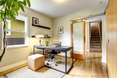 Simple yet practical office room interior. Bright office room interior with tree. Simple black wooden desk with whirlpool chair royalty free stock photo