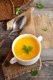 Simple pumpkin soup with potatoes and rice. Pumpkin soup in a bowl, spoon, brown bread slices on old wooden background. Vegetable. Vegetarian recipe. Vegetable Stock Image