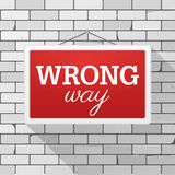 Simple red sign with text `Wrong Way` hanging on a gray brick wall. Grunge brickwork background, textured rough surface. Creative business interior template Royalty Free Stock Photography