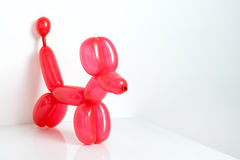 Simple red twisted balloon animal dog on white. Toy of balloons, free space for text. Balloon art. Stock Image