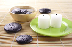 Simple relaxation. Two fragrant candles, some smooth pebbles and water Stock Image