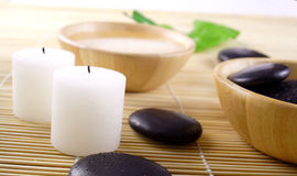 Simple relaxation. Two fragrant candles, some smooth pebbles and water. theme: SPA, purity, health & beauty, relaxation, resort Royalty Free Stock Photos