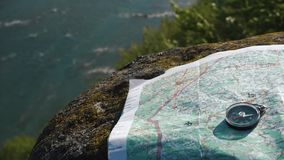 Simple round compass with paper terrain map on the weathered stone near wide mountain stream stock video footage