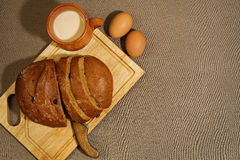 Simple rural breakfast on rude fabric background. Homemade bread with raisins, baked milk and baked eggs on the rude textiled background royalty free stock photos