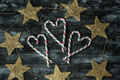 Simple rustic Christmas background with canes and golden stars royalty free stock images