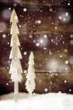 Simple rustic Christmas trees in snow. Two simple rustic Christmas trees cut out of wood standing in snow in front of a wooden wall with falling snowflakes for a Royalty Free Stock Images