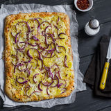 Simple rustic crispy pie with  potatoes, cheese and red onion. Royalty Free Stock Photo