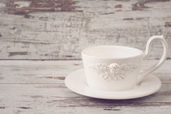 Simple rustic white crockery, empty dishes. A large cup of coffee in front angel. Wooden background, shabby chic, vintage tinting,. Copy space Stock Photo