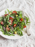 Simple salad with arugula, cherry tomatoes and olives. Royalty Free Stock Photos