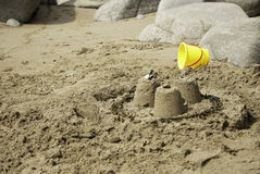 Simple Sandcastles with Yellow Bucket. 3 small simple sandcastles on a sandy beach with large boulders, yellow bucket in background Royalty Free Stock Image