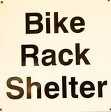 Bike rack shelter sign. A simple sign indicating the presence of a bike rack shelter nearby Royalty Free Stock Photography