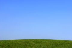 Simple Skyline. Grass hill with a clear blue sky Stock Images