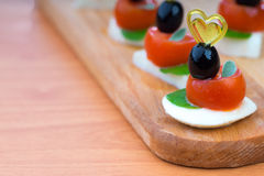 Simple snack canape with tomato, mozzarella and basil Royalty Free Stock Photo