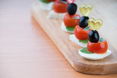 Simple snack canape with tomato, mozzarella and basil Royalty Free Stock Image