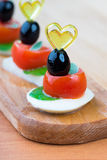 Simple snack canape with tomato, mozzarella and basil Stock Photos