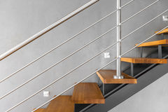 Simple staircase with chromed railing idea. Villa interior with staircase with chromed railing and decorative grey wall finish Stock Photos