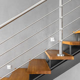 Simple staircase with chromed railing. Villa interior with staircase with chromed railing and decorative grey wall finish Royalty Free Stock Photo