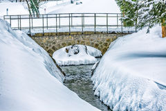 Simple stone bridge over the stream. Simple stone bridge over the small stream at winter time Stock Image