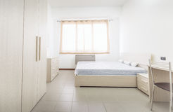 Simple student-style dorm bedroom with lots of light.  Stock Photos