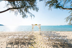 Simple style wedding arch and decoration. Venue, setup on tropical beach, outdoor beach wedding Royalty Free Stock Photography