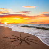 Simple sun drawing in the sand on sunset beach Royalty Free Stock Image