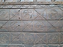 Simple sun symbols carved in wood. Old wooden door of a church Royalty Free Stock Photos