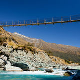 Swing bridge high over glacial river New Zealand Stock Images