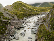 Swing bridge over mountain river in New Zealand Royalty Free Stock Photo