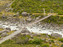 Swing bridge over mountain river in New Zealand Royalty Free Stock Image