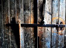 Simple swinging iron bar lock inside an old barn door bathed in bright sunlight. Old oak doors, stained by Royalty Free Stock Images