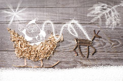 Simple symbols of Father Christmas sleigh arranged from sawdust and reindeer made from dry wooden sticks on wooden grey background Stock Photos